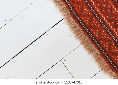White Painted Wood Floor with an Orange Pattern Fringe Rug at an Angle from the Top Right Corner