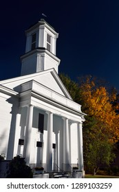 White painted wood North Universalist Chapel Society Woodstock Vermont in Fall with blue sky Woodstock, Vermont, United States - October 11, 2014