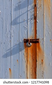 White painted wood stained by the rusty fittings on a door with padlock