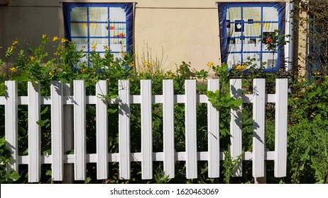 White painted wooden fence in front of yellow wall of house facade with two fake windows. Blooming flowerbed of colorful flowers growing behind white fence. Tranquil landscape of springtime.
