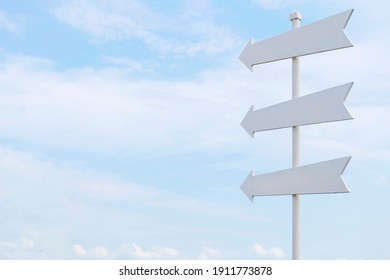 White painted wooden sign with an arrow pointing out on sky background.