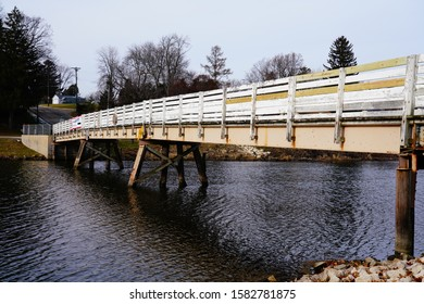 White painted wooden walking path bridge extended over Rock River in Mayville, Wisconsin