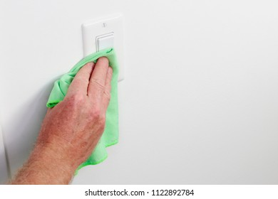 White panel light control cleaned by hand cloth. Male hand dusting light switch with cleaning cloth Flat white light switch control being dusted and cleaned with a green cloth by a caucasian male hand