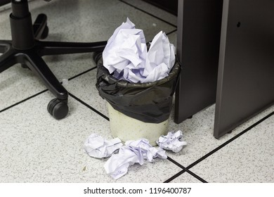 White paper balls into trash in work office, concept office life