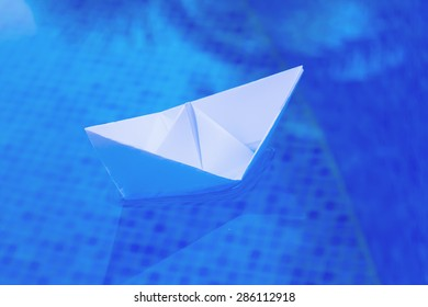 white paper boat floating in blue water - concept of travel