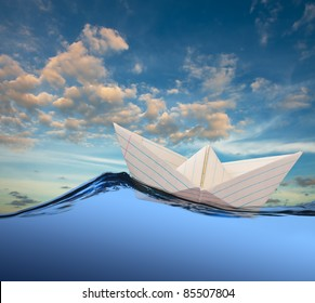 White paper boat floating in the sea.