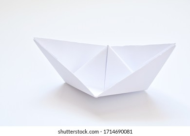 A white paper boat lies on a white surface - concept with the colour white  - Shutterstock ID 1714690081