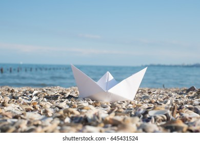 White paper boat on beach at sunset time