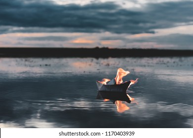 White paper boat on fire floating in the river at sunset