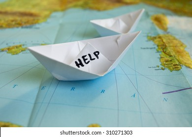 "White paper boat onto world map with ""Help"" sign on it."