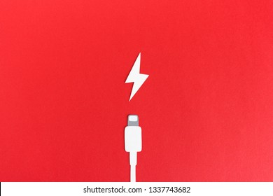 White paper cable and icon of charging composed on red backdrop