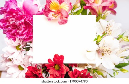 White paper card note laying in bright flowers bouquet. Romantic wedding invitation. Present for women. Birthday greeting card. Mother`s day. Space for text. Place for text