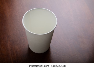 a White paper coffee cup on table.