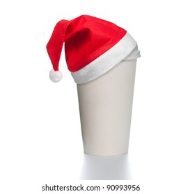 White paper coffee cup with plastic cap on top. Blank space for copy on cup and besides. Red santa christmas hat on top of the cup. Square format.