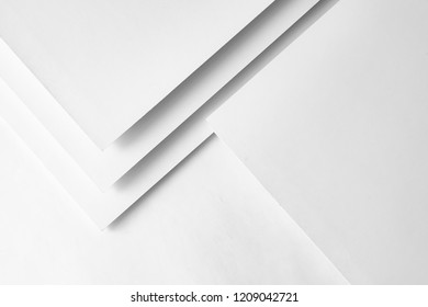 White paper concept background with cardboard shadow and copy space. Geometric layer design with group of paper sheets