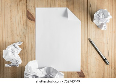 white paper and crumpled paper and gray pencil on wooden background