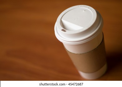 White paper cup of coffee on a wooden table.