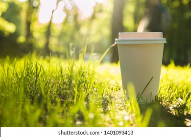 White paper Cup with lid with coffee on green grass
