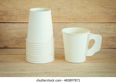 White paper cup on wood background vintage and grain picture style