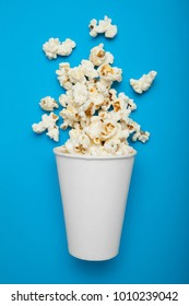 White paper cup with popcorn, mock up. Copy space.