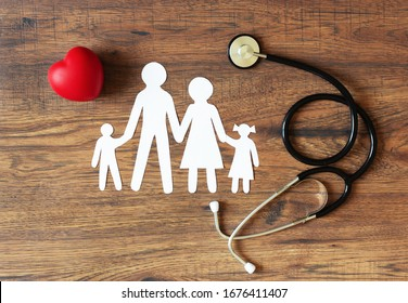 White paper cut of family, stethoscope and heart on wooden background top view. Health medical insurance concept.