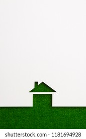 white paper cutout in basic house shape with border background by green flannel, for ecology and energy conceptual.