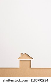 white paper cutout in basic house shape with border background by brown paper, for home and insurance conceptual.