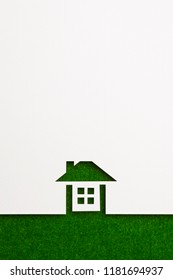 white paper cutout in complete house shape with border background by green flannel, for ecology and energy conceptual.