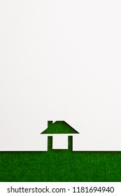 white paper cutout in easy house shape with border background by green flannel, for ecology and energy conceptual.