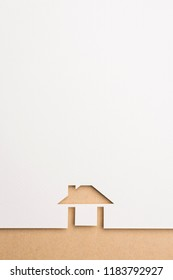 white paper cutout in easy house shape with border background by brown paper, for home and insurance conceptual.