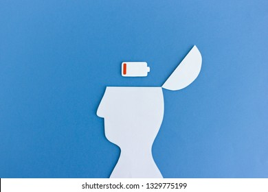 White paper cutout of man with empty battery symbol in opened head on blue background