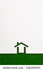 white paper cutout in minimal house shape with border background by green flannel, for ecology and energy conceptual.
