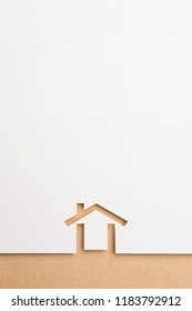 white paper cutout in minimal house shape with border background by brown paper, for home and insurance conceptual.