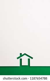 white paper cutout in minimal house shape with border background by green paper, for home, ecology and energy conceptual.