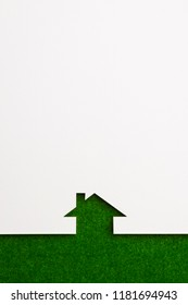 white paper cutout in simple house shape with border background by green flannel, for ecology and energy conceptual.