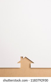 white paper cutout in simple house shape with border background by brown paper, for home and insurance conceptual.