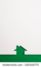 white paper cutout in simple house shape with border background by green paper, for home, ecology and energy conceptual.