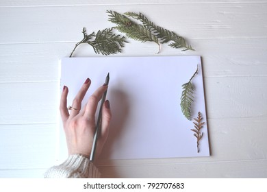 White paper with decoration on the white wooden desk, top view. The pencil in woman's hand.