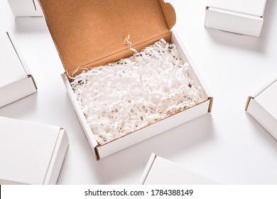 White paper filler in cardboard box, set of white carton boxes