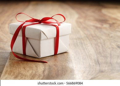 coffret cadeau en papier blanc avec noeud mince en ruban rouge sur vieille table en bois, avec espace pour copie