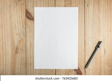white paper and gray pencil on wooden background