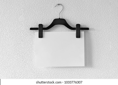 White paper hanging on clothespins on black clothes hanger on screw on grey textured  wallpaper background. Mock up template with hanger for trouser and skirt and blank piece of paper, copy space