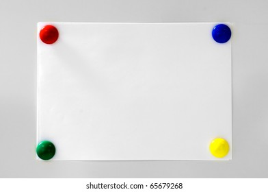 White paper hanging on grey background with four magnets colored blue, red, green and yellow