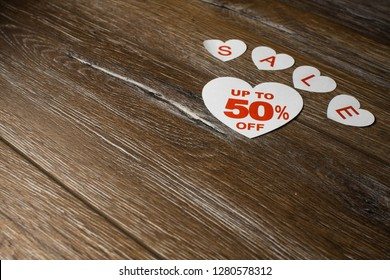 White paper heart with discount up to 50 percent and smaller hearts with letters for word sale isolated on brown wooden background.