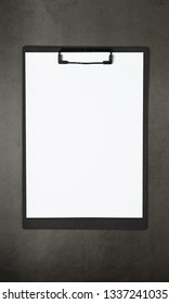 White paper on black clipboard on dark grey background, flat lay, mock up for business, education and design