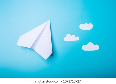 White paper origami airplane lies on pastel blue background, top view.