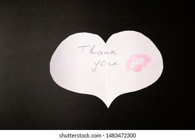 """White paper origami heart with note """"Thank you"""" and print of female lips - kiss pink color is on the black table/background. International Thank You Day"""