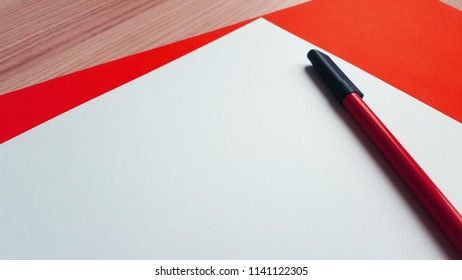 a white paper and a pen in front of a red paper