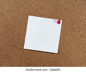 White paper pinned to a corkboard with a pink pushpin.