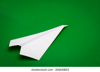 white paper plane on green paper background